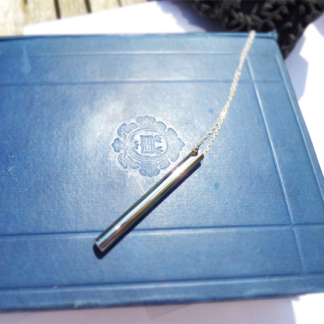 Stainless Steel Cylinder Memorial Pendant on a book