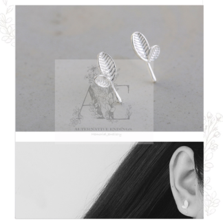 Silver Small Leaf Ear Stud pair and one earring worn by model