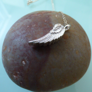 Silver Angel Wing Memorial Pendant on a stone